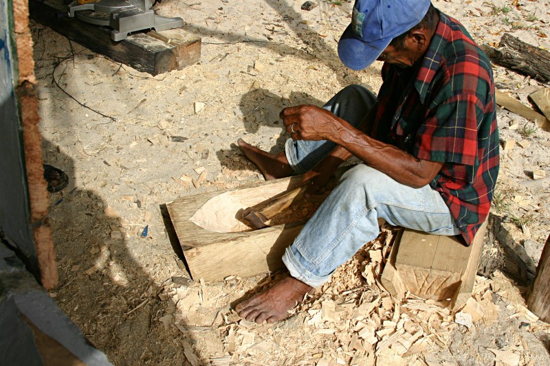 Carib craftsman from Dominica hand-hewing parts to repair damage to Gli Gli.