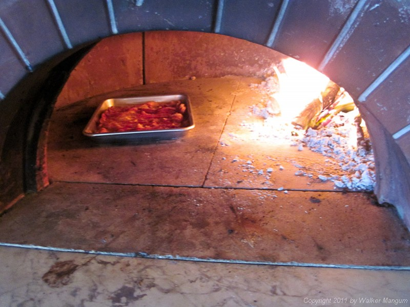 A pound of bacon cooking in Davide's pizza oven. Filet pignon.